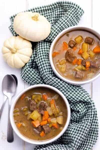 two bowls of stew with spoons and a forest green napkin on a white wood background