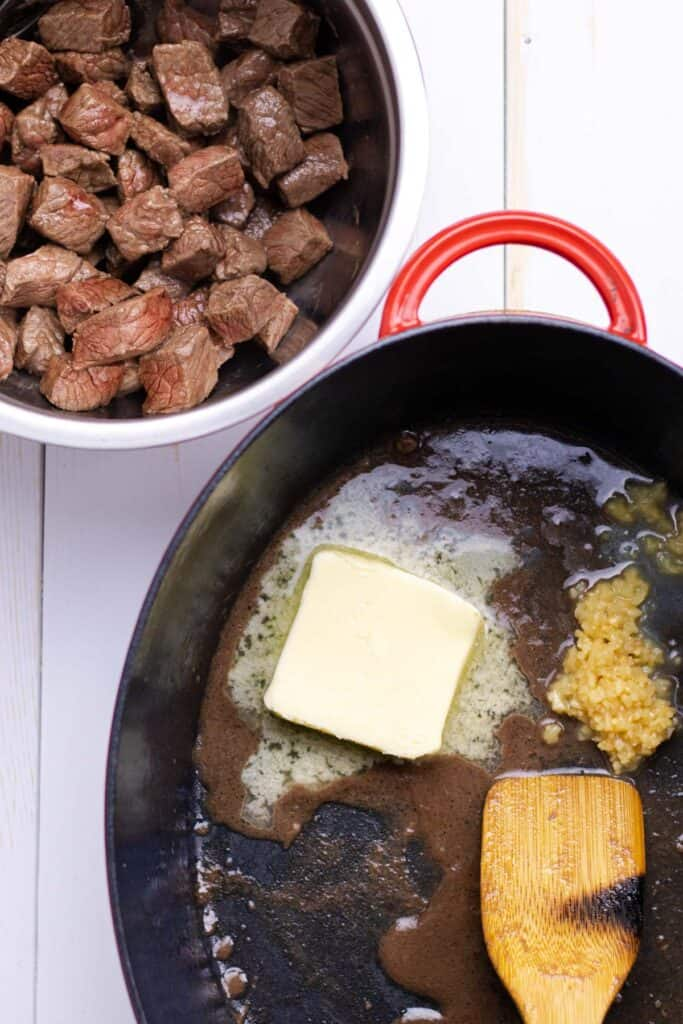 removing the browned meat and melting the butter in the dutch oven