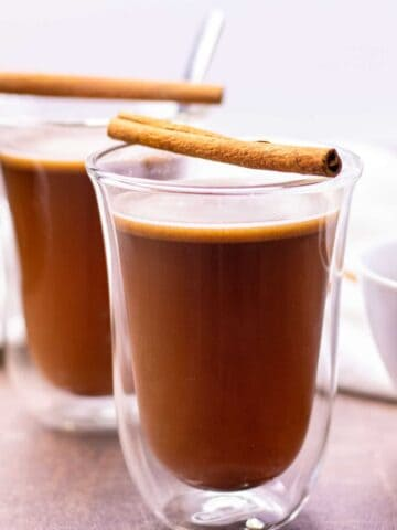 two prepared hot buttered rums in glass coffee mugs, each served with a cinnamon stick on top