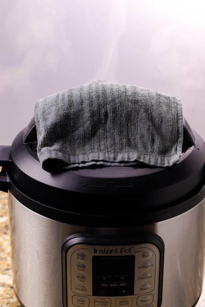 placing a towel overtop of the valve while the pressure is releasing from the pressure cooker