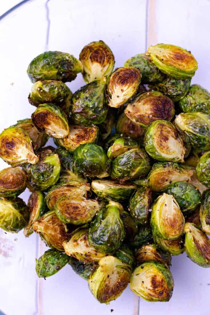 placing the baked brussel sprouts into a mixing bowl