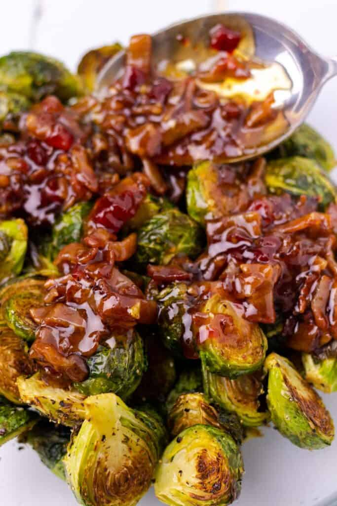 adding the prepared bacon jam to the baked brussel sprouts