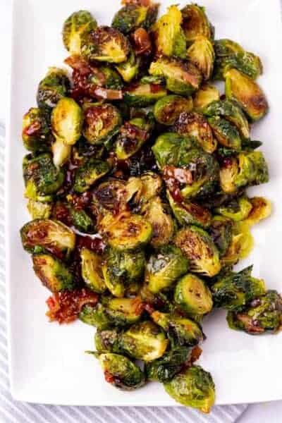 spicy bacon jam brussel sprouts on a white rectangular serving plate