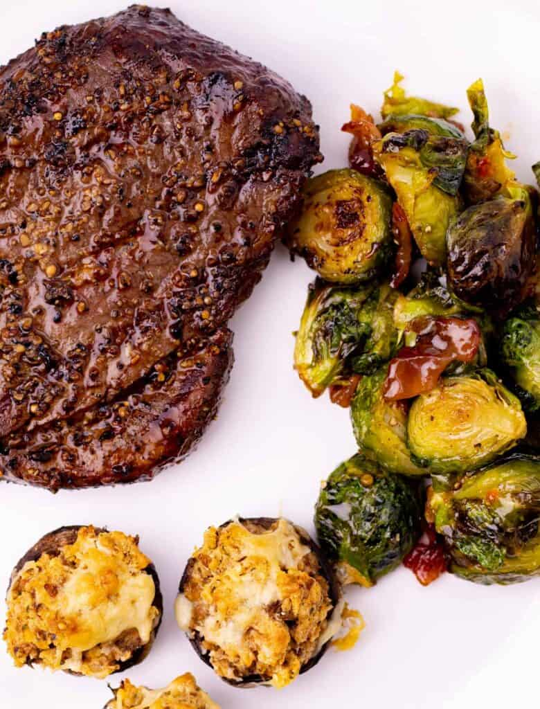 serving the spicy bacon jam brussel sprouts with a steak and cheesy stuffed mushrooms