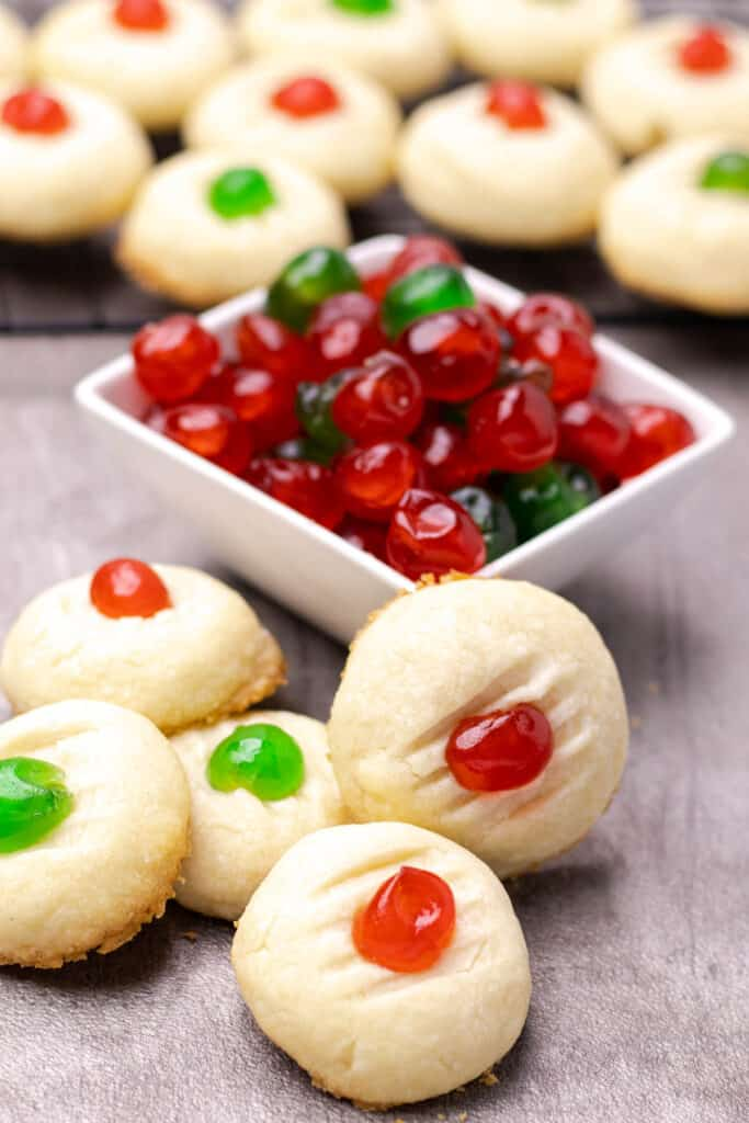 a pile of whipped shortbread cookies next to a bowl of glace cherries