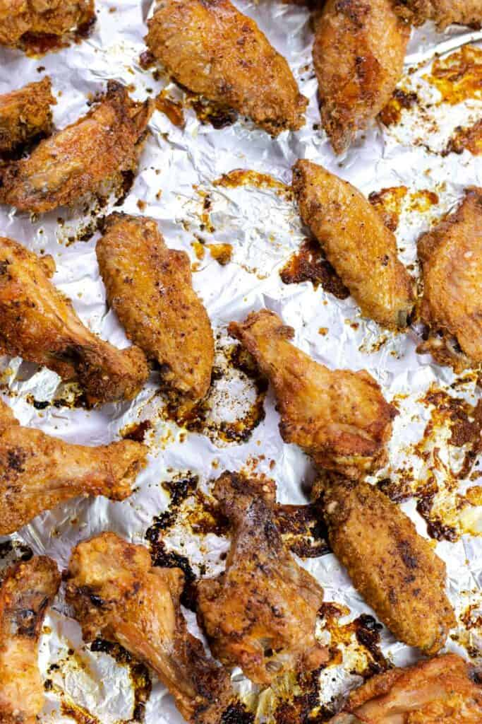 crispy baked chicken wings after they have finished baking on a baking sheet lined with aluminum foil