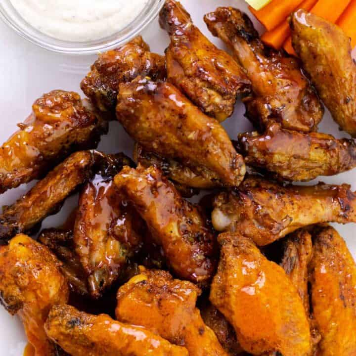 serving honey garlic wings and buffalo wings with a side of dipping sauce and vegetables