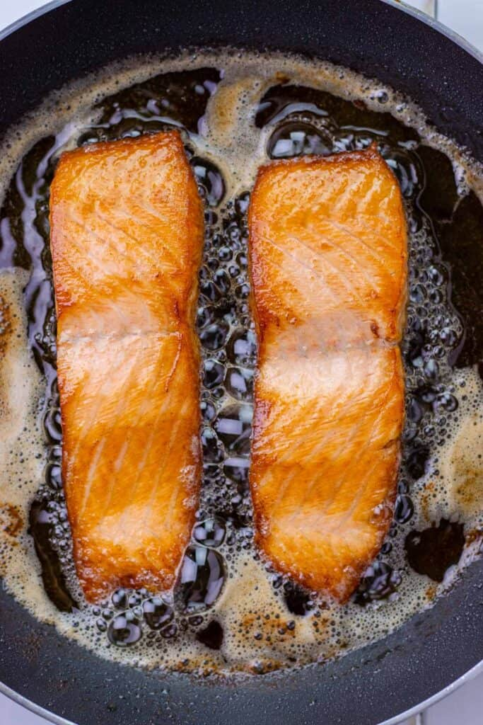 Golden brown salmon filets after they have been flipped in the skillet