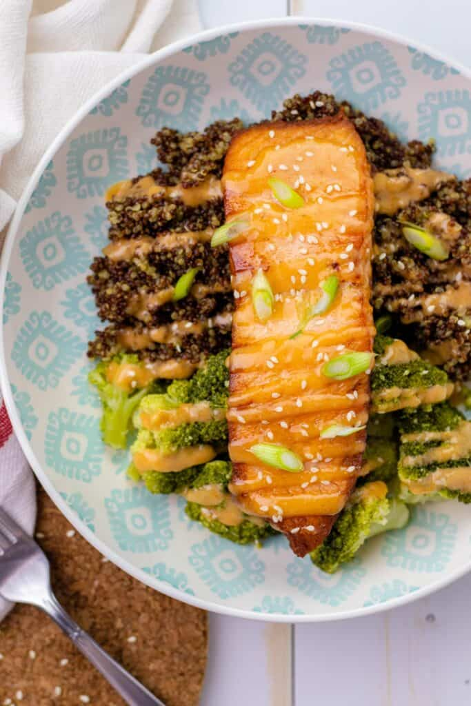 pan fried salmon served with steamed broccoil and quinoa, and topped with firecracker aioli sauce
