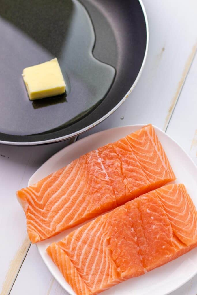 two 6oz salmon filets on a white plate and a skillet with oil and butter ready to cook