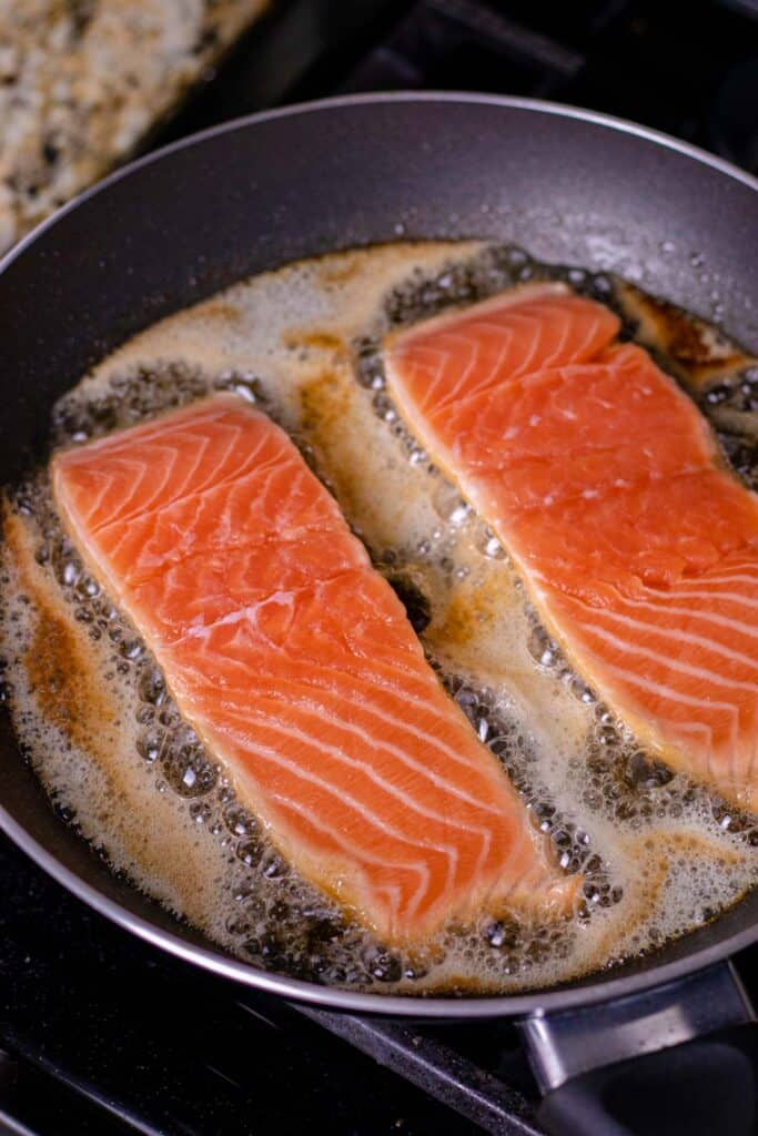 pan searing the salmon in the butter/oil mixture on the stove