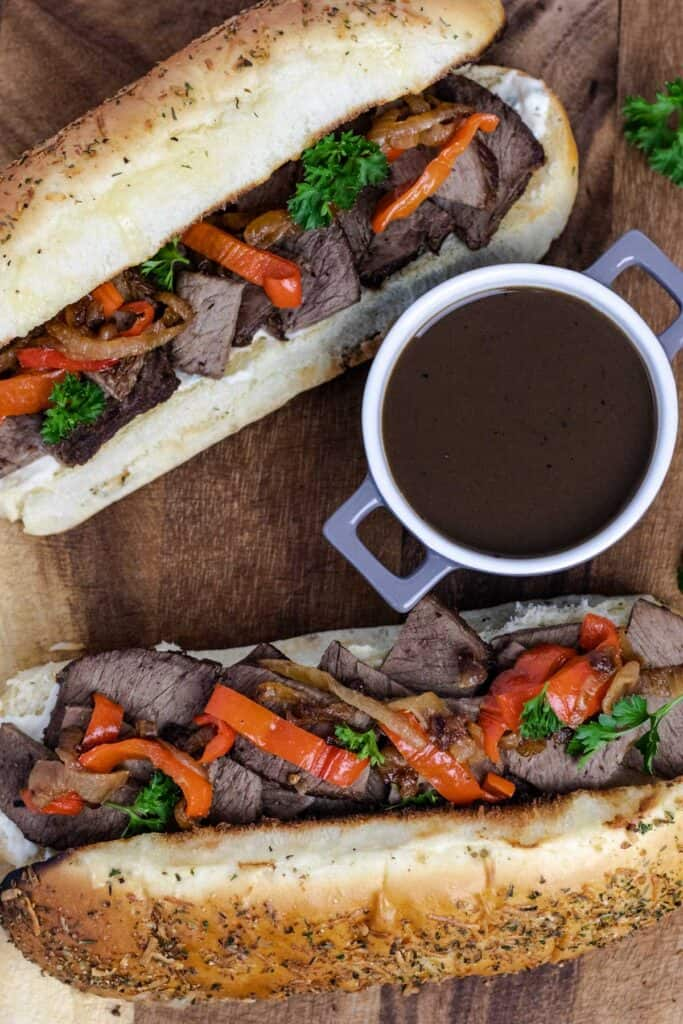 two prepared beef dip sandwiches with a side of au jus