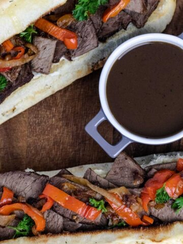 beef dip sandwiches with horseradish mayo prepared on a butchers block and served with a side of au jus