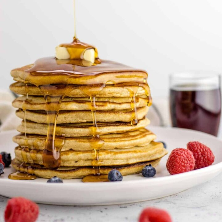 a fresh stack of pancakes with a pad of butter on top and syrup drizzled all over