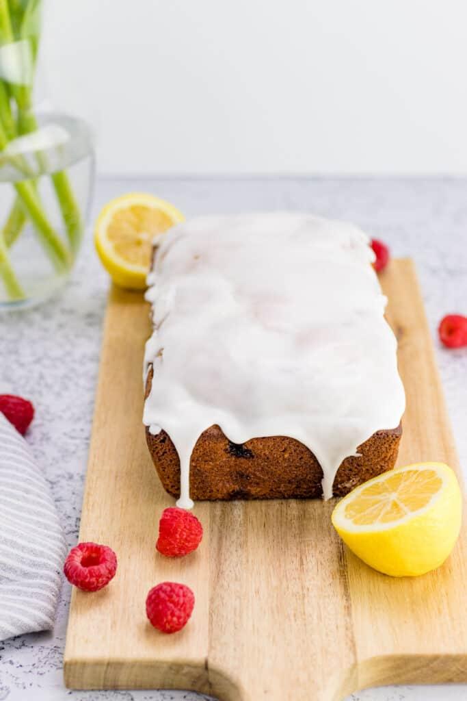 completed raspberry lemon loaf on a wooden serving board