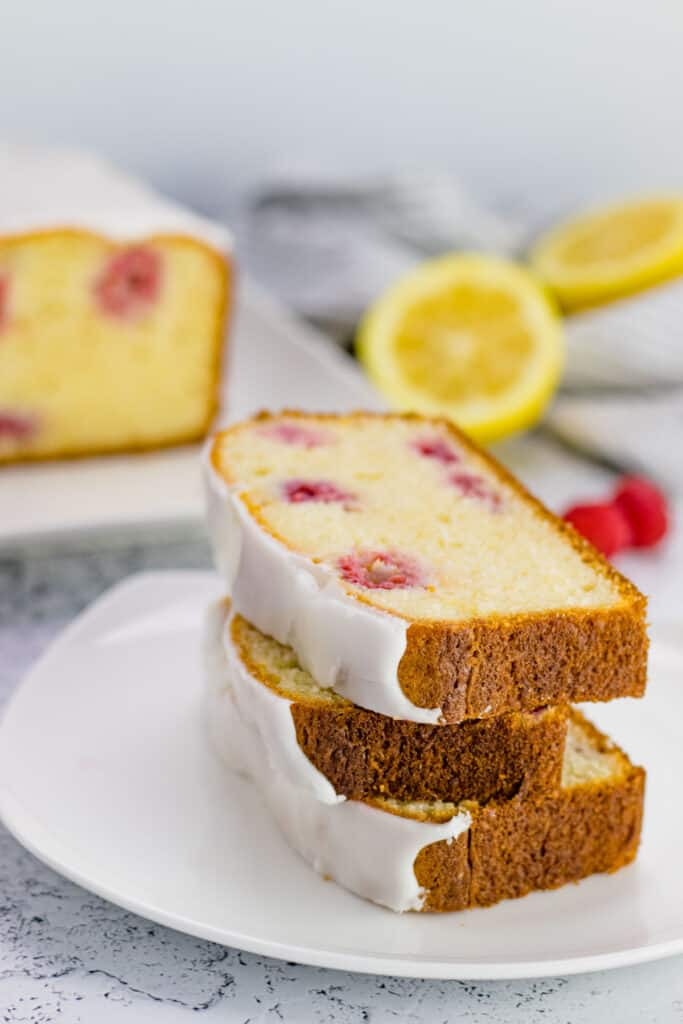 a stack of raspberry lemon loaf slices on a white plate