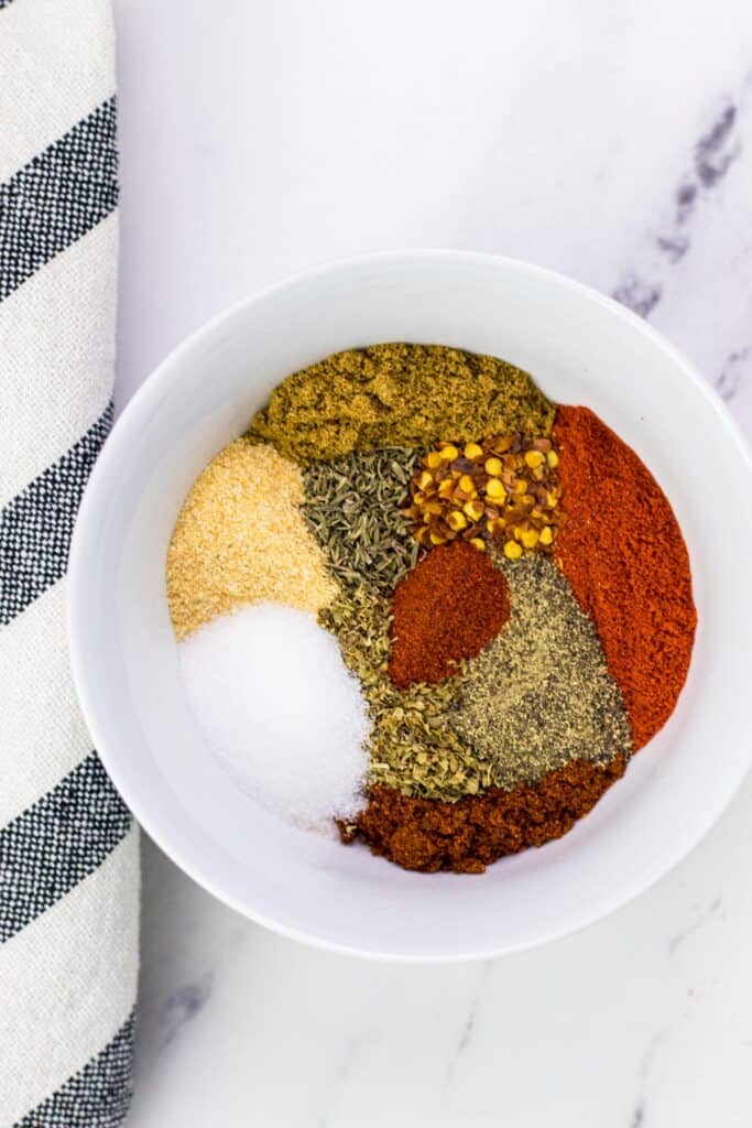 all of the ingredients to make taco seasoning in a small white mixing bowl
