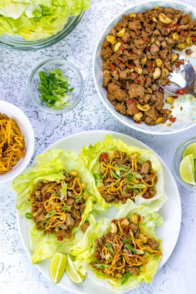 turkey lettuce wraps with extra turkey filling, crispy noodles, lime wedges and scallions in serving dishes on the side