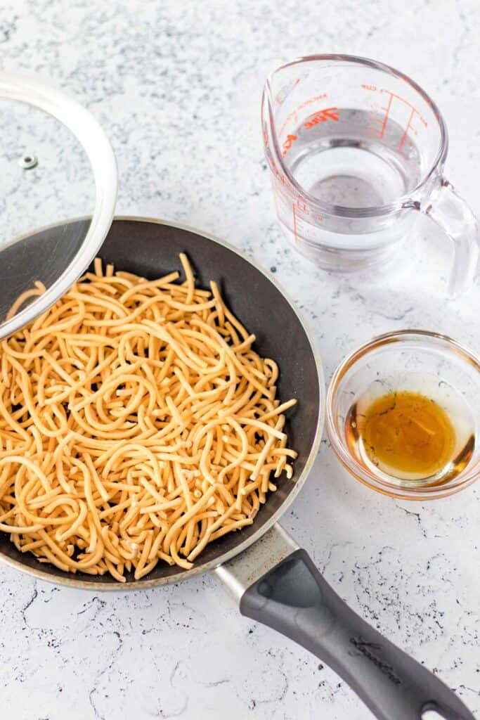 adding the dry chow mein noodles to a small fry pan with the water and oil on the side