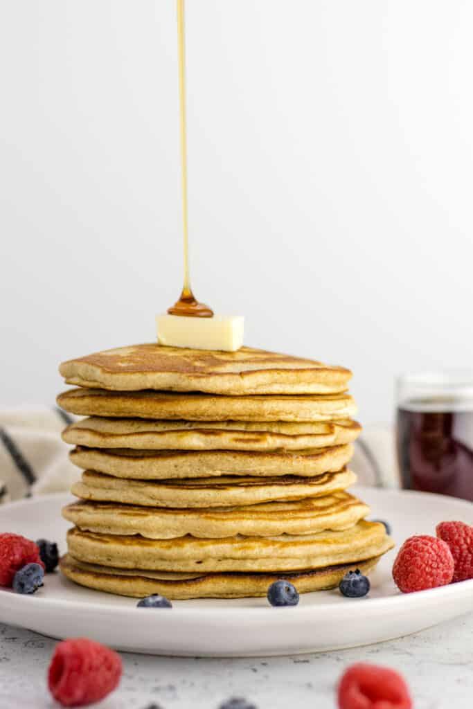 pouring syrup onto the stack of pancakes