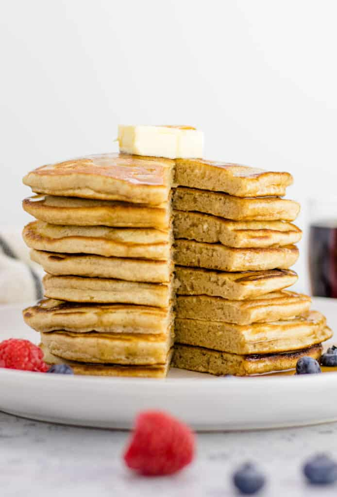 cutting open the stack of pancakes to show how fluffy the insides are