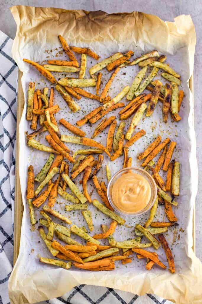 baked sweet potato fries after they have finished baking on a parchment paper lined baking sheet