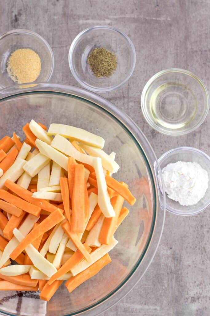 a bowl of raw sweet potato fries with all of the spices on the side
