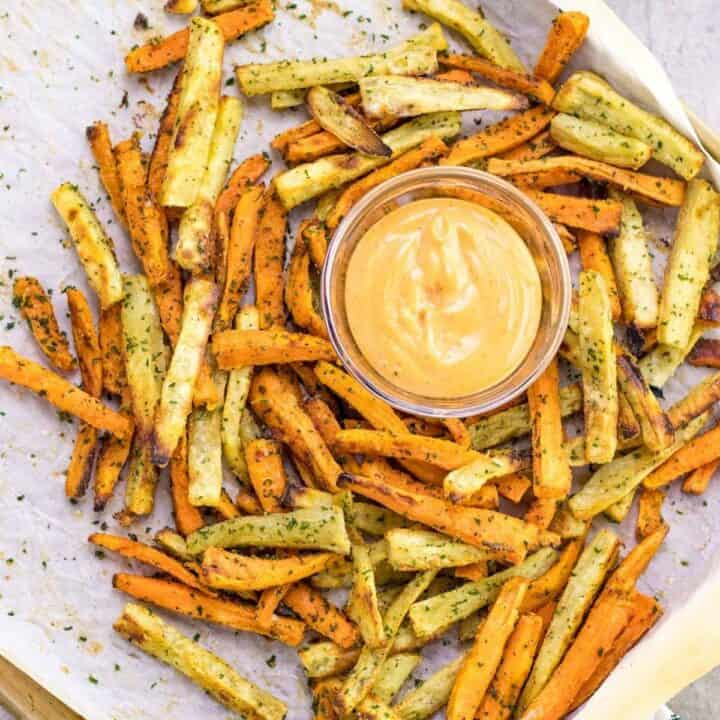 a pile of sweet potato fries on a baking sheet with a side of aioli