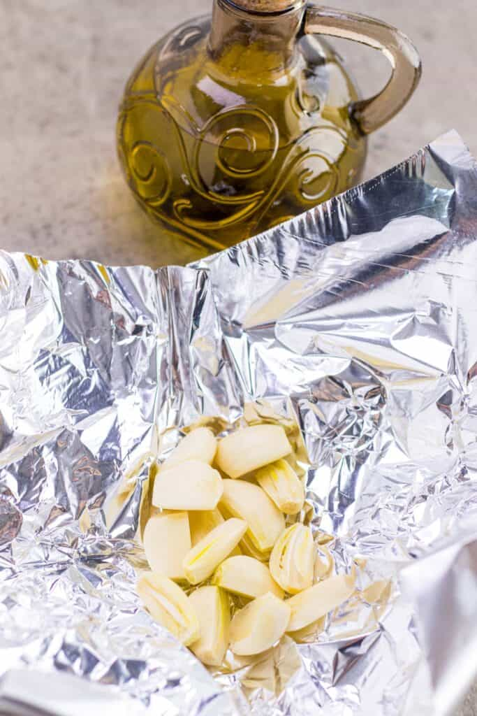 placing the peeled garlic cloves into a piece of aluminum foil