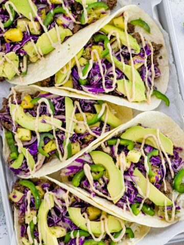 a pan full of spicy caribbean beef tacos with squeezed limes on the side