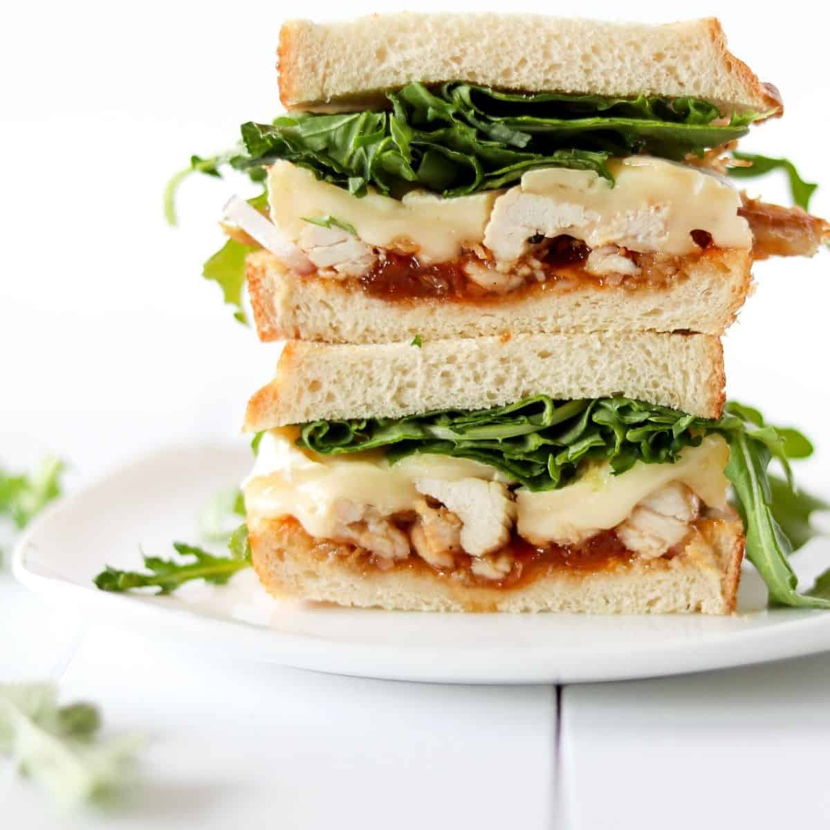 Apricot brie chicken sandwich stacked on a white plate