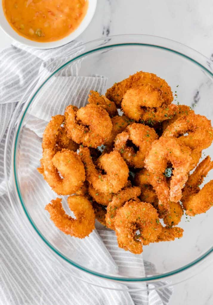 crispy fried shrimp in a large clear mixing bowl with the bang bang sauce on the side