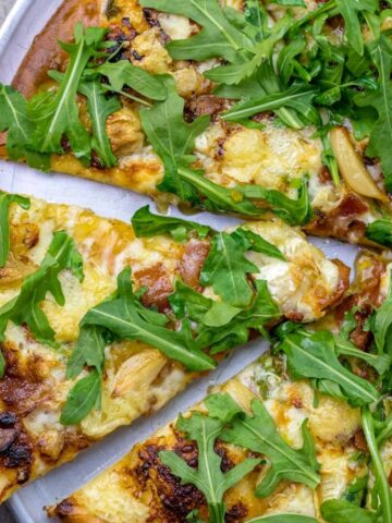 a slice of camembert, fig, roasted garlic, and arugula pizza