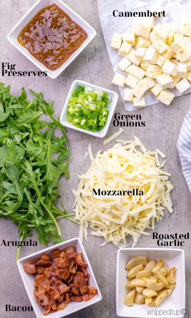 the ingredients required to make the pizza are camenbert cheese, fig preserves, green onions, mozzarella, arugula, bacon, and roasted garlic