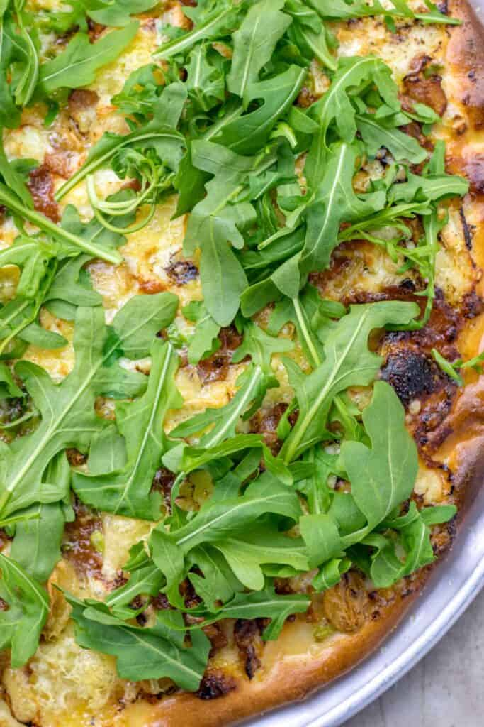 a close up of the baked pizza after adding the arugula on top.