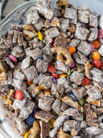 muddy buddies in a large glass mixing bowl