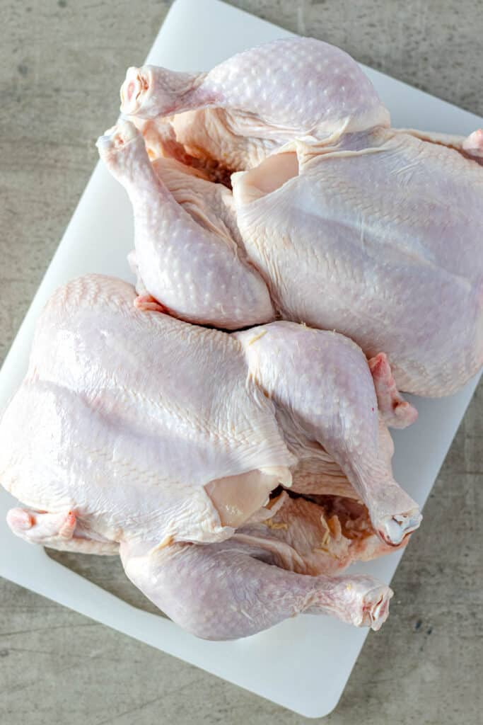 two whole uncooked chickens on a white cutting board