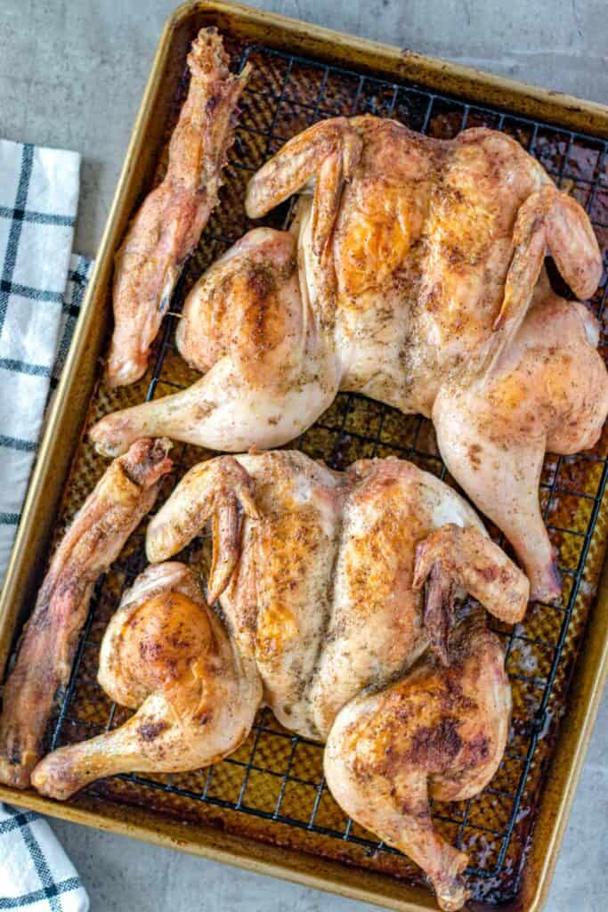 two fully cooked spatchcocked chickens on a baking sheet