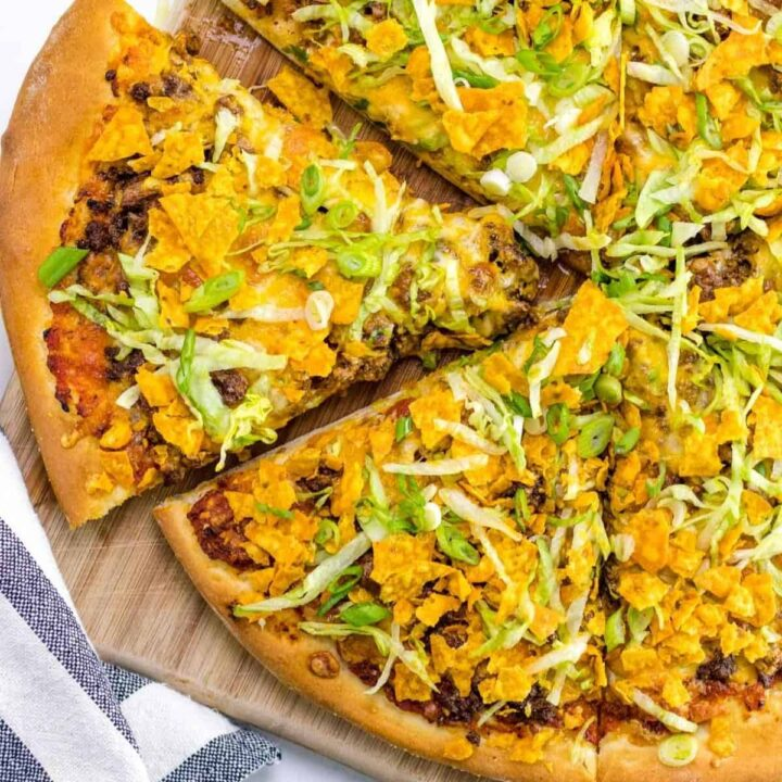 prepared nacho pizza on a wooden serving board