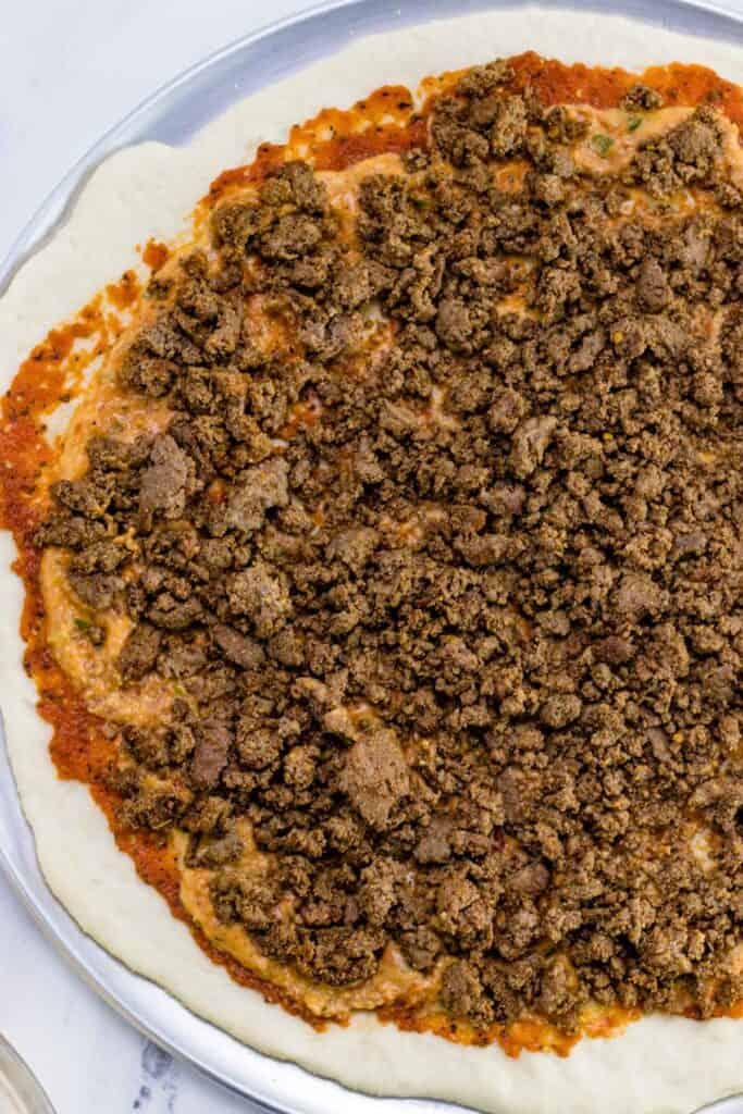 adding spiced ground beef on top of the sauces