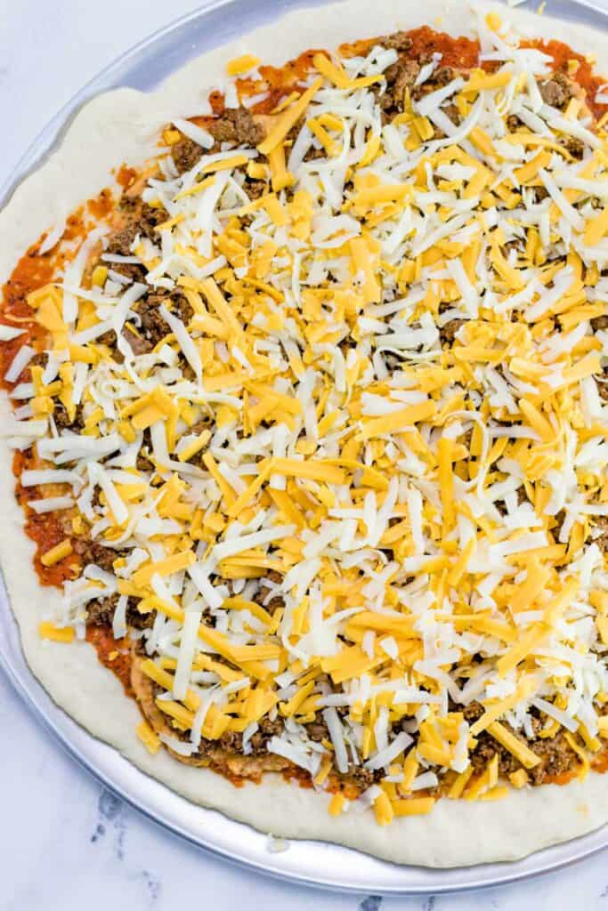 covering the ground beef layer with shredded cheddar and mozzarella cheese
